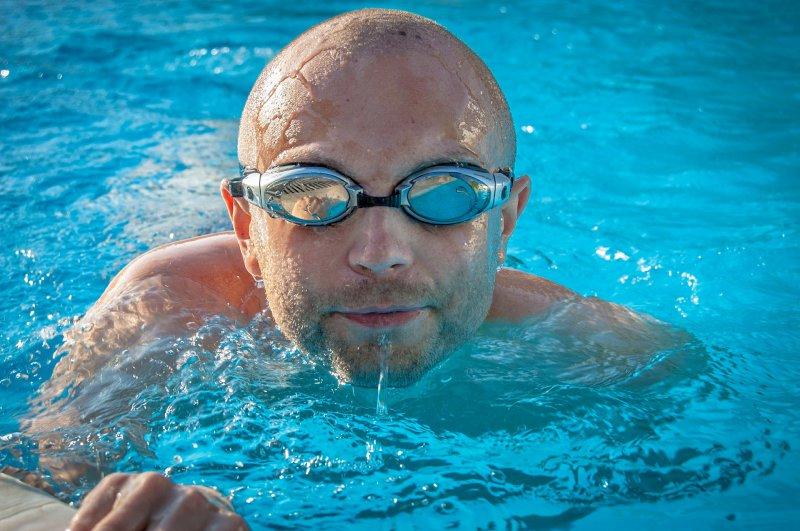 Mann im Wasser mit einer Schwimmbrille