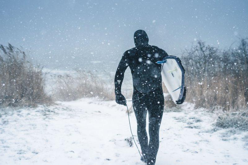 Surfer trägt Neoprenmütze im Winter