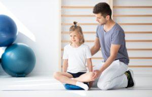 Mädchen macht Physiotherapie mit einem Ballsitzkissen