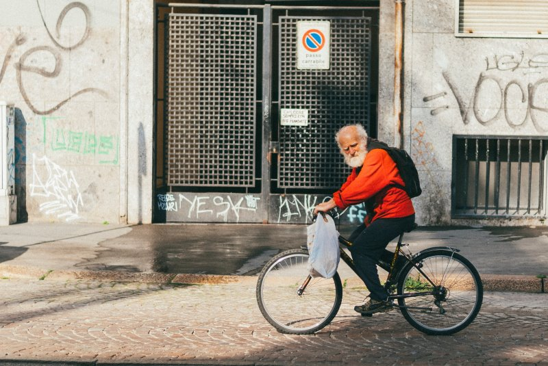 Ein Senior fährt auf seinem Tourenrad durch die Stadt