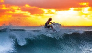 Surfer mit Surfer-Sonnenbrilleauf einer Welle mit Sonnenuntergang im Hintergrund