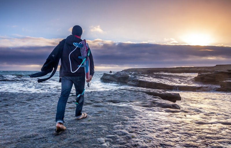 Surfer am Meer trägt Neoprenmütze