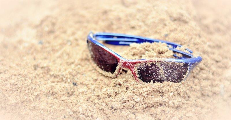 Surfer-Sonnenbrille liegt im Sand