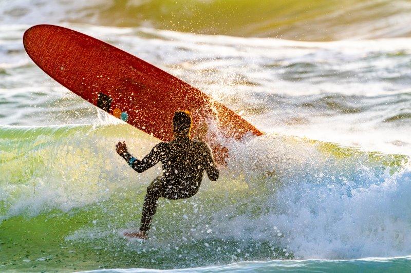Surfer wird von einer Welle vom Surfboard geworfen.