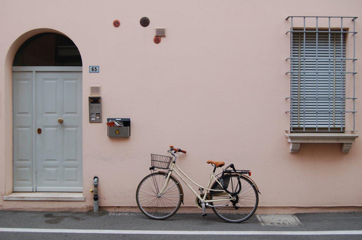 Ein Tourenrad mit Fahrradkorb und Gepäckträger vor einer Hauswand