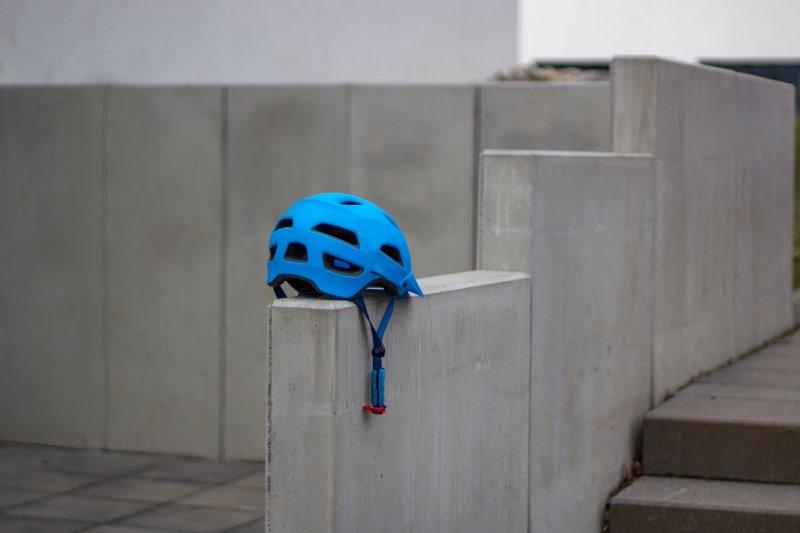 Ein blauer Fahrradhelm auf einer grauen Mauer