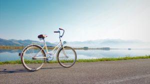 Ein Tourenrad auf einer befestigten Straße mit einem See im Hintergrund