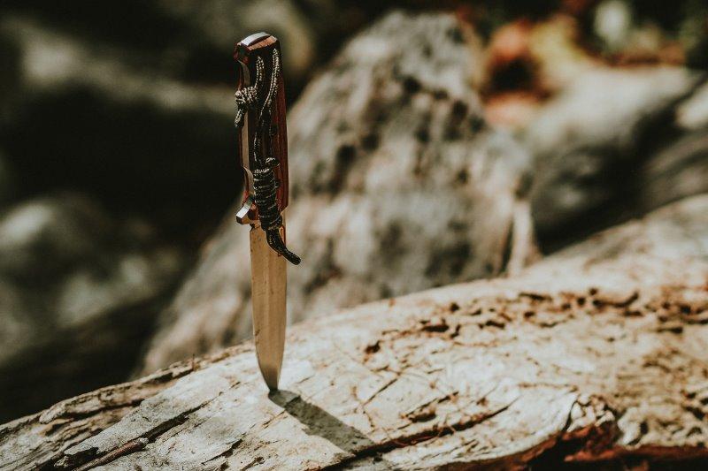 Outdoormesser steckt in Holz