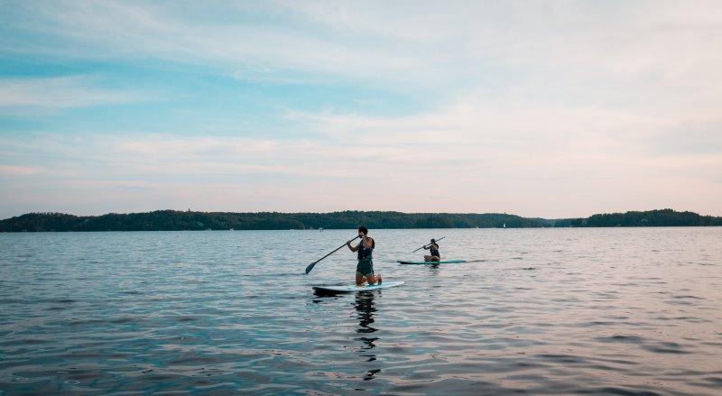 Zwei Personen auf aufblasbaren SUP auf großem See