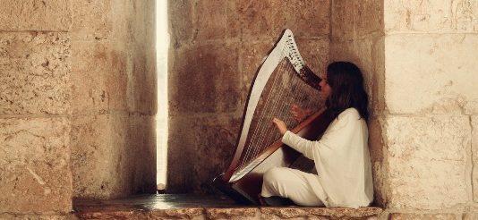 Weiß gekleidete Frau mit Harfe, in der Hand.