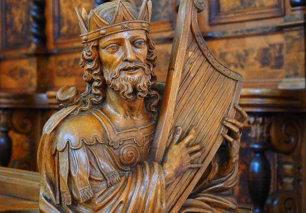 Statur eines Mannes mit einer Harfe, in Holzbrauner Farbe.