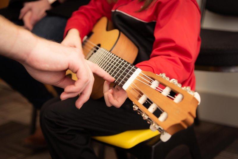 Kind sitzt auf einem Stuhl und lernt Gitarre