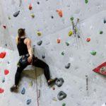 Frau klettert eine Kletterwand hoch