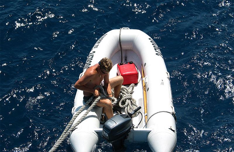 Mann mit Schlauchboot im Meer