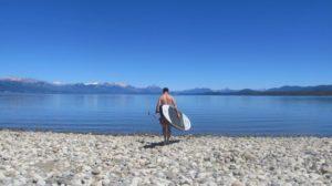 SUP-Boarder steht an einem See vor einer Bergkulisse