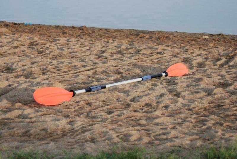 SUP-Doppelpaddel liegt am Strand
