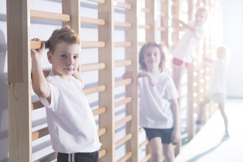 Kinder turnen in einer Turnhalle an einer Sprossenwand