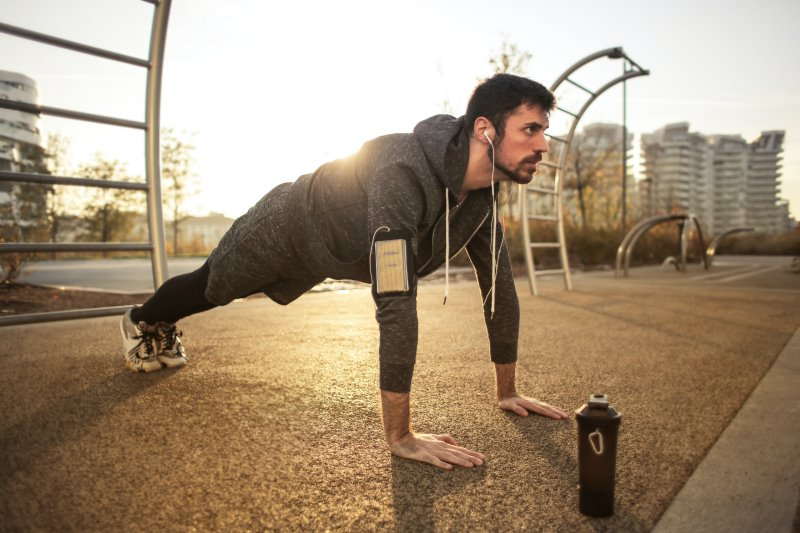 Mann macht draußen an einer Sprossenwand Sport