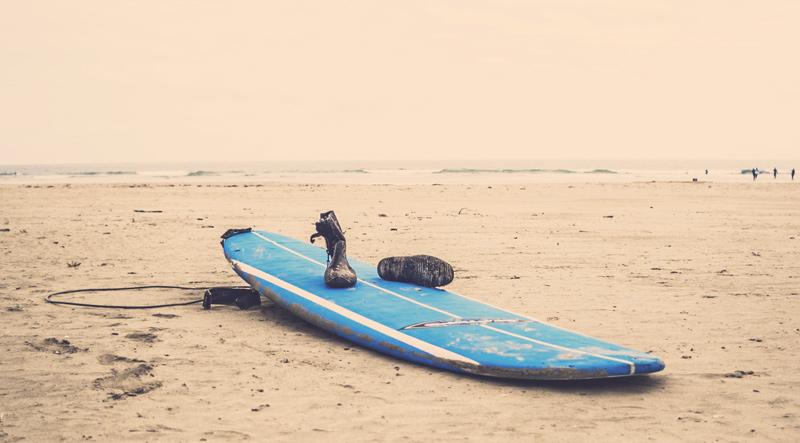 Wasserschuhe auf einem Surfbrett am Strand