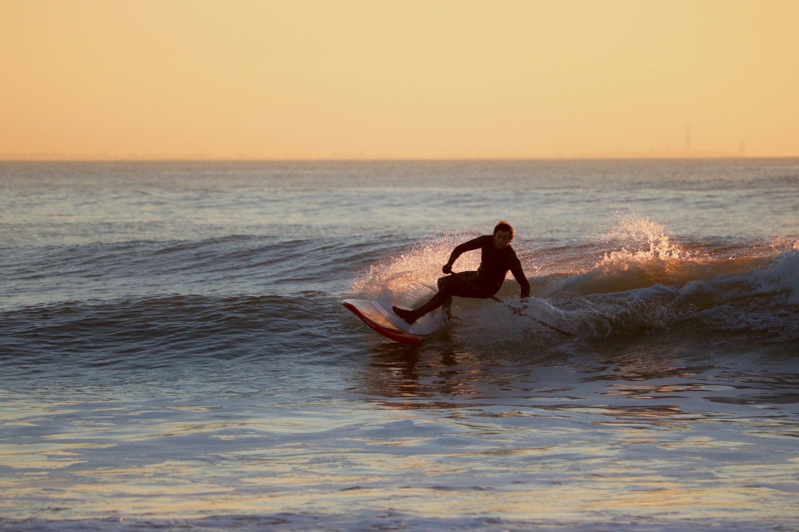 SUP-Waveboarder auf Welle mit SUP-Paddel