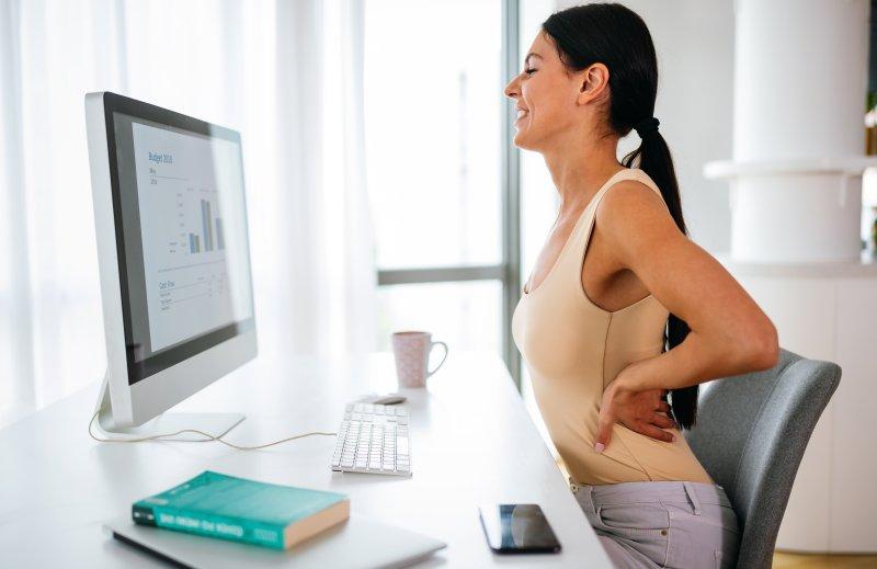 Frau hat Rückenschmerzen vor dem Computer