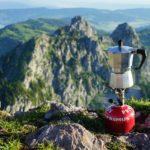 Gaskartusche mit Kocheraufsatz und Kaffeekanne auf einem Berggipfel