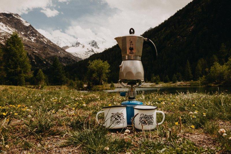 Kaffeekanne auf einem Gaskocher mit zwei Tassen in den Bergen