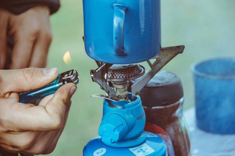 Ein Gaskocher wird mit einem Feuerzeug angezündet.