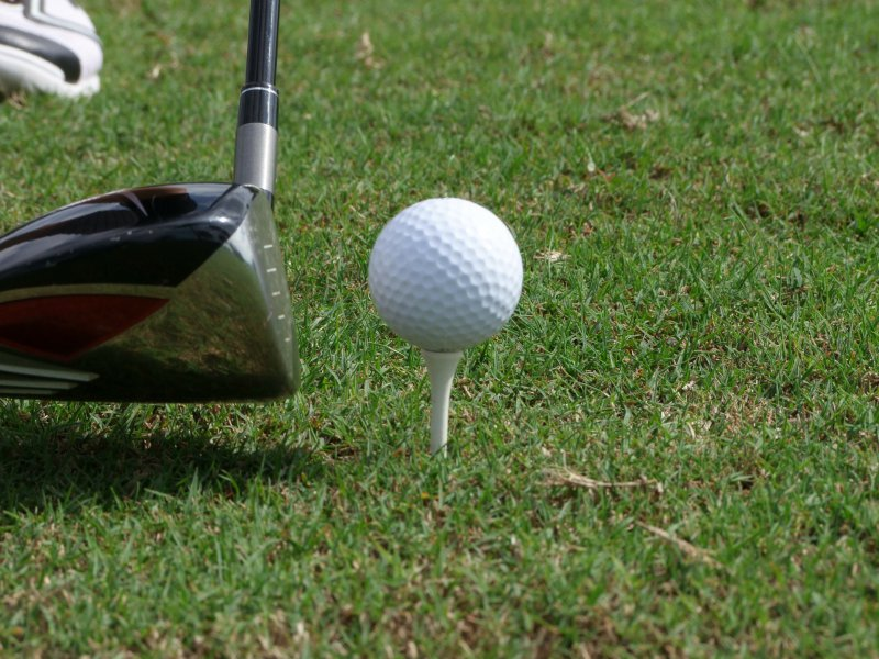 ein Golfschläger hinter einem Golfball