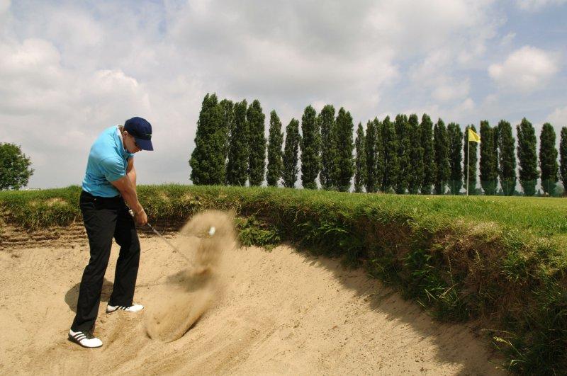 Golfball wird mit dem Golfschläger aus dem Sand geschlagen
