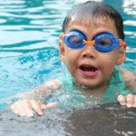 Junge mit blau/orangener Schwimmbrille