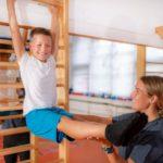 Kind und Sporttrainer trainieren zusammen an einer Sprossenwand
