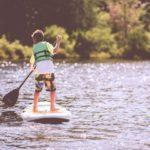 Ein Junge steht auf einem SUP und trägt eine Schwimmweste.
