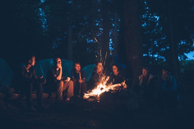 Freunde sitzen beim Campen zusammen am Lagerfeuer