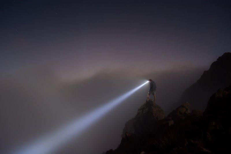 Ein Mann leuchtet mit seiner Stirnlampe den Berg herunter