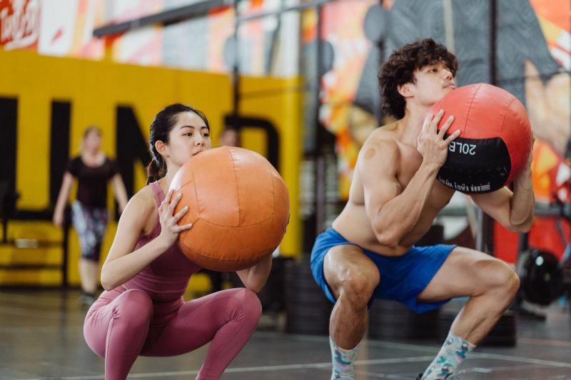 Ein Mann und eine Frau trainieren mit Medizinbällen