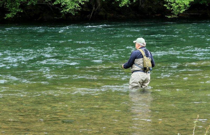 Ein Mann angelt mit einer Neopren Wathose im Fluss.