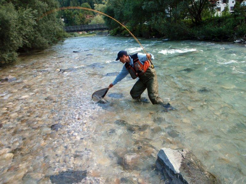 Ein Mann in Neopren Wathose mit Angel und Kescher angelt im Fluss.