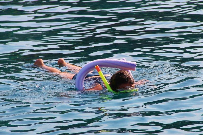Kind schwimmt mit Poolnudel in Wasser