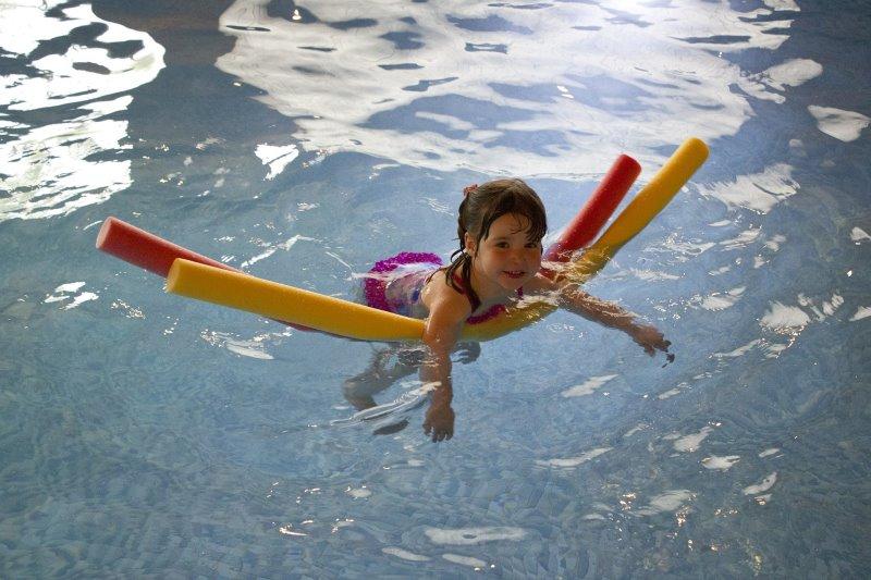 Kind lernt Schwimmen mit Poolnudel