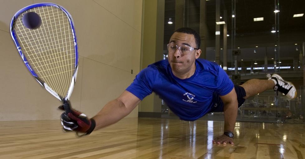 Squashspieler schlägt Ball im Flug
