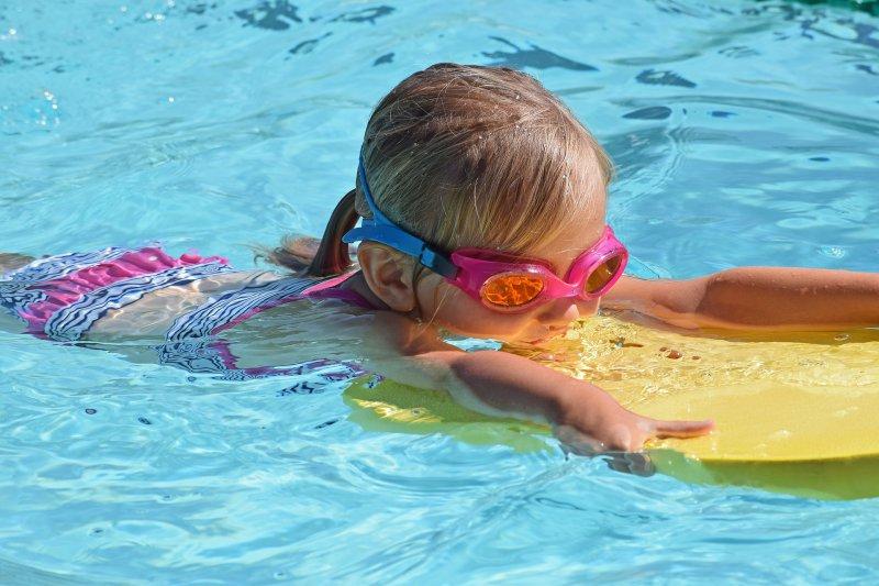 Mädchen lernt Schwimmen mit einem Schwimmbrett im Wasser.