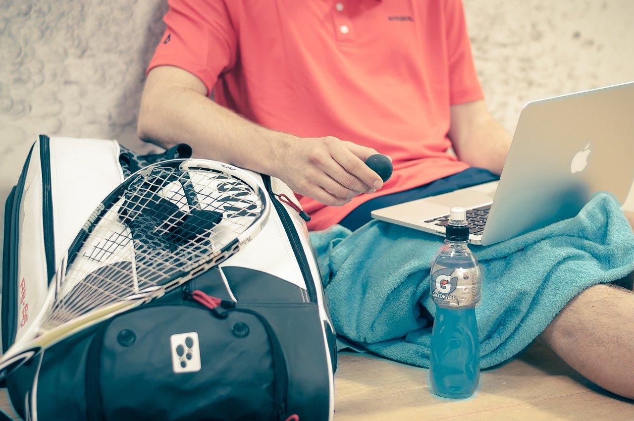 Squashspieler sitzt mit Laptop auf dem Schoß