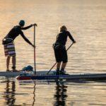 Zwei Personen betreiben Stand-Up-Paddling auf dem Meer bei Sonnenuntergang und tragen dabei SUP Socken.