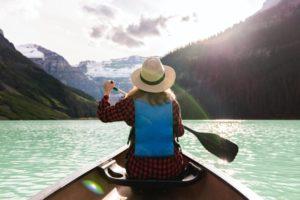 Frau mit Hut auf See und Stechpaddel in der Hand