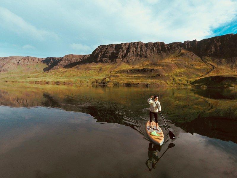 Eine Frau steht auf einem SUP Board in einem See. Das SUP kann man mit einer Elektropumpe aufpumpen.