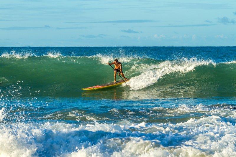 Ein Mann steht auf einem SUP und surft in einer Welle.