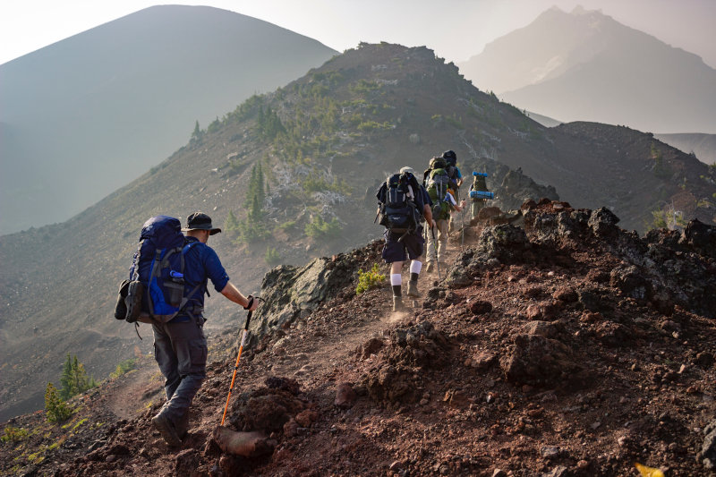 Personen wandern im Gebirge mit Ausrüstung