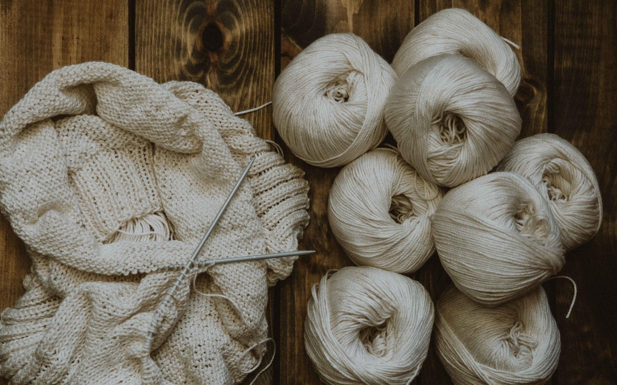 Wollknaeule mit Strickprojekt und Stricknadeln