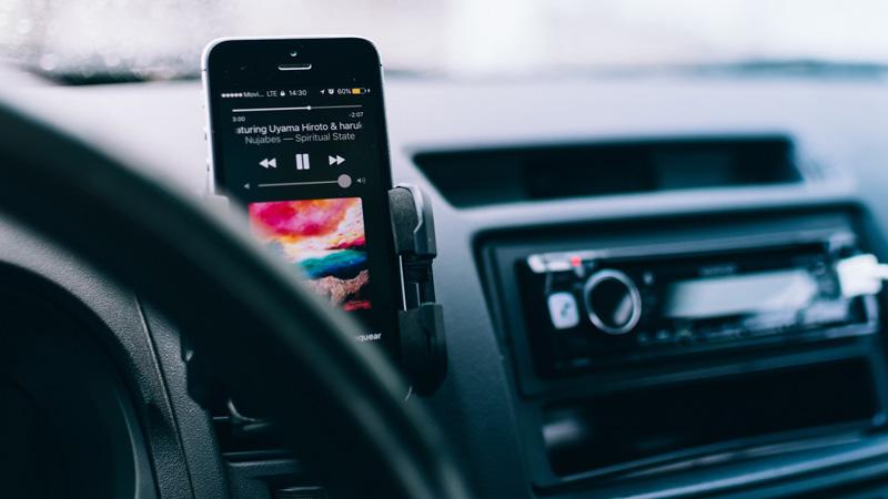 Smartphone mit laufendem Musikplayer in einem Auto neben dem Lenkrad befestigt und mit einem Autoradio im Hintergrund